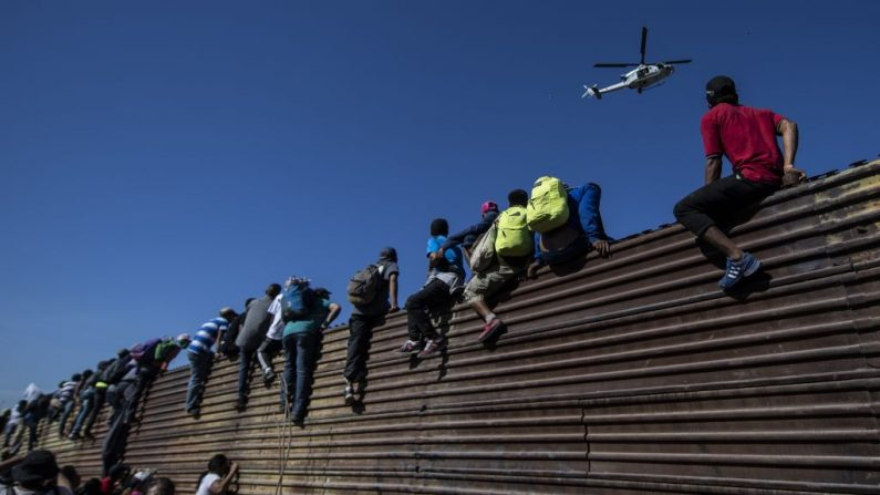 Un grupo de migrantes centroamericanos -en su mayoría hondureños- escalan una barrera metálica en la frontera entre México y Estados Unidos, cerca del paso fronterizo de El Chaparral, en Tijuana, Estado de Baja California, México, el 25 de noviembre de 2018. Foto de PEDRO PARDO/AFP/Getty Images.