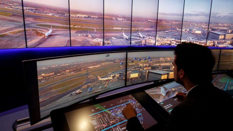 Los ingenieros de control de tráfico aéreo utilizan pantallas que muestran vistas panorámicas en tiempo real de las pistas y puertas de embarque dentro de la torre de control del Aeropuerto Heathrow de Londres, en el oeste de Londres, el 23 de enero de 2019. (TOLGA AKMEN/AFP/Getty Images)