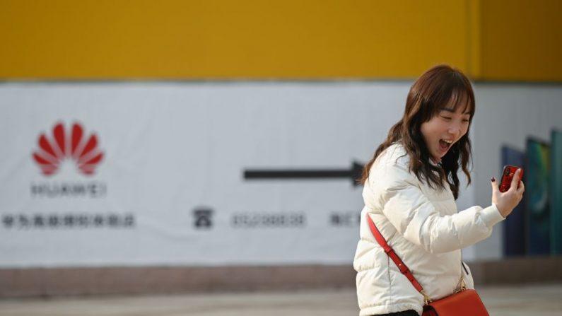 Una mujer ríe mientras usa su teléfono móvil frente a una tienda Huawei en Beijing el 29 de enero de 2019. - Los mercados asiáticos cayeron el 29 de enero cuando el gigante chino Huawei en los EE.UU. proyectó una sombra sobre las próximas conversaciones comerciales, mientras que los inversores también rastreaban una venta en Wall Street alimentada por la preocupación de las ganancias corporativas. (Foto de WANG ZHAO/AFP) (El crédito de la foto debe ser WANG ZHAO/AFP/Getty Images)