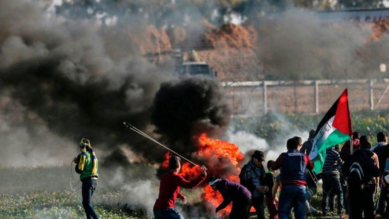 Los manifestantes palestinos queman neumáticos durante una manifestación cerca de la valla a lo largo de la frontera con Israel, al este de la ciudad de Gaza, el 22 de febrero de 2019. - Un adolescente palestino fue asesinado hoy por fuego israelí durante los enfrentamientos a lo largo de la frontera de Gaza..(Foto de MAHMUD HAMS/AFP) (Crédito de la foto debe leer MAHMUD HAMS/AFP/Getty Images)