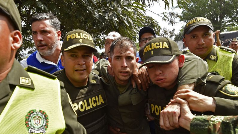 Policías colombianos acompañan a un policía venezolano que desertó al régimen de Nicolás Maduro en el puente internacional Simón Bolívar, en Cúcuta, Colombia. ( LUIS ROBAYO/AFP/Getty Images)