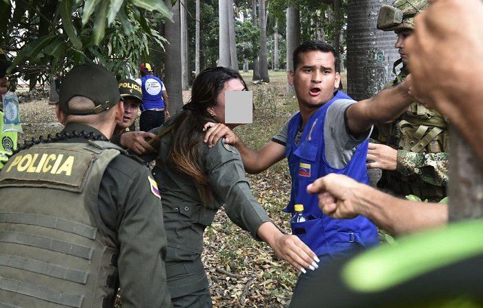 Una mujer miembro de las Fuerzas Armadas Nacionales Bolivarianas (FANB) (C) que desertó, saluda a un pariente que permanece en Venezuela mientras es escoltada por agentes de la policía colombiana cerca del puente internacional Simón Bolívar en Cúcuta, Colombia, el 23 de febrero de 2019. (LUIS ROBAYO/AFP/Getty Images)