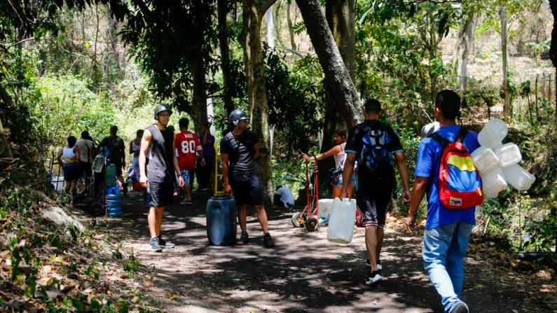 La gente camina con tanques y botellas para llenarlos con el agua que proviene de la montaña durante los apagones de luz, que afecta a las bombas de agua el 12 de marzo de 2019 en Caracas, Venezuela. Más del 70% del país estaba en la oscuridad. El gobierno de Juan Guaidó acusa a la dictadura de Nicolás Maduro por la situación que vive el país. (Eva Marie Uzcategui/Getty Images)