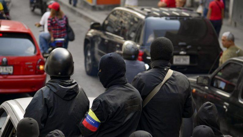 """Los miembros enmascarados de un """"colectivo"""", las células del régimen Nicolás Maduro, asisten a un mitin en Caracas el 7 de enero de 2019. Los miembros de """"Colectivo"""" son denominados  revolucionarios y matones, según YURI CORTEZ/AFP/Getty Images)"""