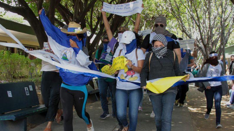 Estudiantes participan en una manifestación convocada por la Universidad Centroamericana (UCA) de Nicaragua para conmemorar los 11 meses del inicio de las protestas antigubernamentales y exigir la liberación de los opositores a Daniel Ortega detenidos durante dichas protestas, en Managua el 18 de marzo de 2019. Foto de MAYNOR VALENZUELA/AFP/Getty Images.
