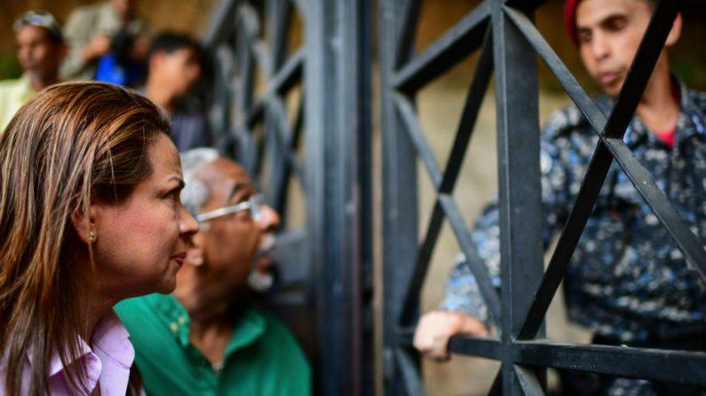 La diputada Dennis Fernández habla con un miembro de la guardia bolivariana del régimen de Maduro en la entrada del cuartel general del Servicio de Inteligencia Bolivariano (SEBIN) en Caracas, donde llegó para solicitar información sobre la detención de Roberto Marrero, el jefe de personal del presidente interino Juan Guaidó, el 22 de marzo de 2019. RONALDO SCHEMIDT/AFP/Getty Images)