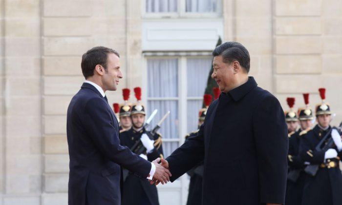 El presidente francés Emmanuel Macron (izq.) recibe al líder chino Xi Jinping en el Palacio del Elíseo en París durante una visita de Estado, el 25 de marzo de 2019. (LUDOVIC MARIN/AFP/Getty Images)