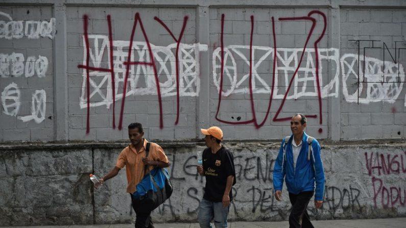 Peatones pasan junto a un graffiti que dice:'¿Hay luz? durante un apagón en Caracas el 26 de marzo de 2019. Un nuevo apagón barrió Venezuela, incluyendo gran parte de Caracas, sembrando alarma dos semanas después de un apagón nacional que paralizó el país. (FEDERICO PARRA/AFP/Getty Images)