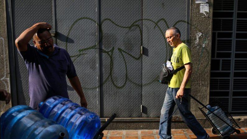 Un trabajador (L) entrega bidones de agua en Caracas el 27 de marzo de 2019 durante un corte de energía en Venezuela, mientras que un cierre de 24 horas de escuelas y lugares de trabajo se ha extendido otras 24 horas para eliminar una carga de la red. (CRISTIAN HERNANDEZ/AFP/Getty Images)