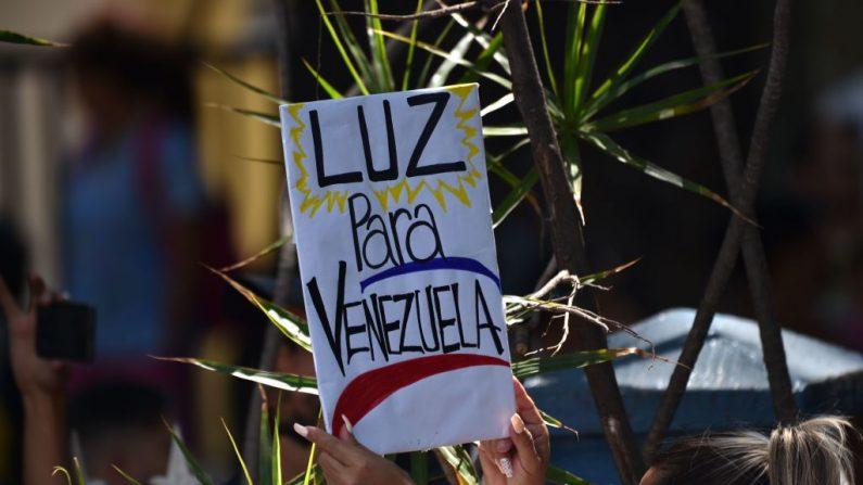 """Una mujer sostiene un cartel que dice """"Luz para Venezuela"""" en Caracas el 27 de marzo de 2019. La desesperación y la rabia se extiende entre los venezolanos a medida que pasan las horas y el apagón masivo que golpea al país no se resuelve. (YURI CORTEZ/AFP/Getty Images)"""