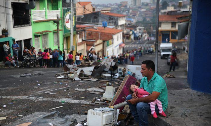 Antes del amanecer, un padre y su hija descansan mientras alguien conserva su lugar en una larga fila para comprar alimentos básicos en un supermercado en San Cristóbal, la capital del estado de Táchira, Venezuela, el 8 de marzo de 2014. (John Moore/Getty Images)
