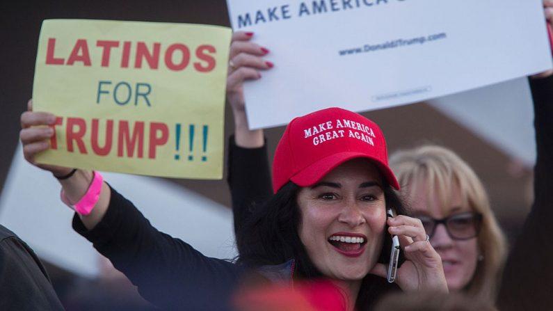 Una mujer encubre una señal que expresa el apoyo latino al candidato presidencial republicano Donald Trump en su mitin de campaña el 28 de abril de 2016, en Costa Mesa, California. (DAVID MCNEW/AFP/Getty Images)