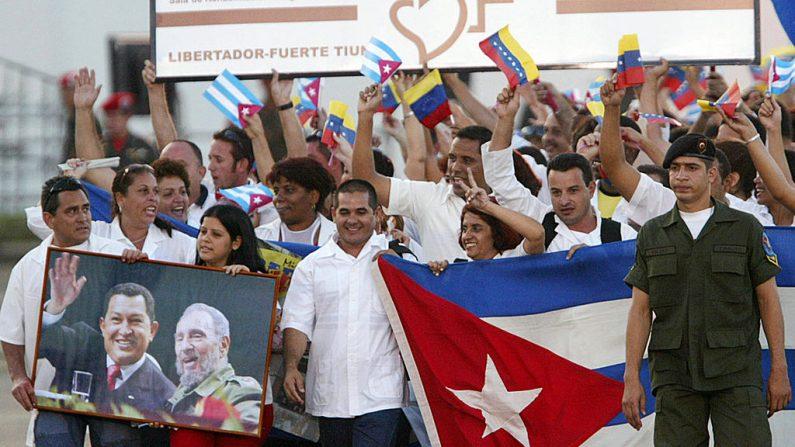 Médicos cubanos de la misión Barrio Adentro participan en un desfile militar portando una foto del expresidente venezolano Hugo Chávez (I en la foto con su homólogo cubano Fidel Castro) en el patio del Fuerte Tiuna en Caracas. (ANDREW ALVAREZ/AFP/Getty Images)