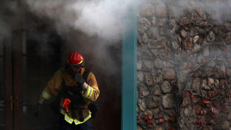 Un bombero protege su cara del humo mientras intenta extinguir un incendio en una casa durante el incendio de Tubbs el 12 de octubre de 2017 cerca de Calistoga, California. (Foto de Justin Sullivan/Getty Images)