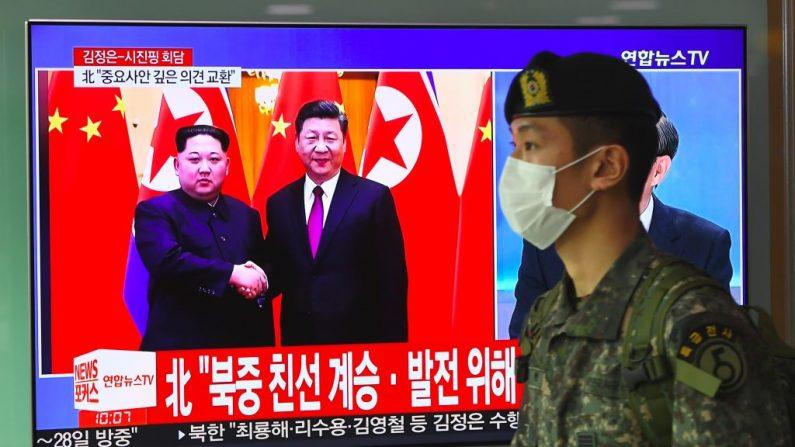 Un soldado surcoreano pasa por delante de una pantalla de televisión que informa sobre la visita a China del líder norcoreano Kim Jong Un, en una estación de ferrocarril de Seúl, el 28 de marzo de 2018. (JUNG YEON-JEON/AFP/Getty Images)