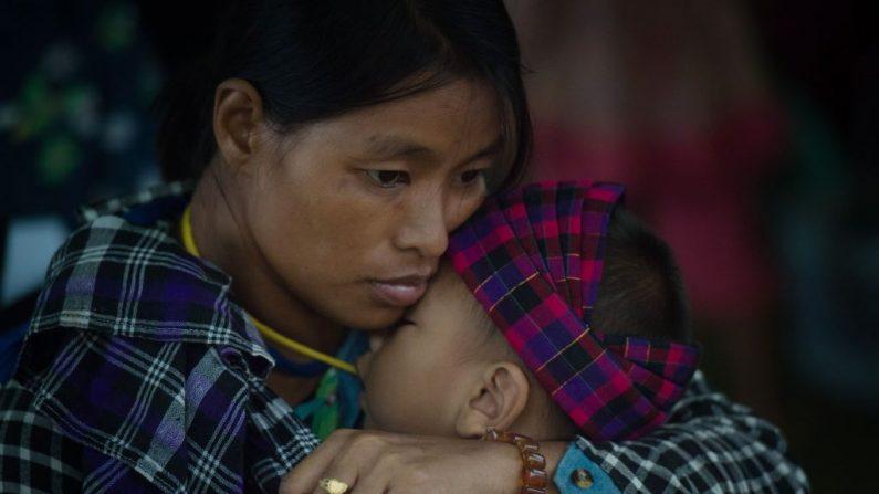 En esta foto tomada el 13 de mayo de 2018, una mujer internamente desplazada y un niño están en un refugio temporal en un recinto de la iglesia en Myitkyina, estado de Kachin a causa del conflicto entre la guerrilla y el Estado de Birmania (E AUNG THU/AFP/Getty Images)
