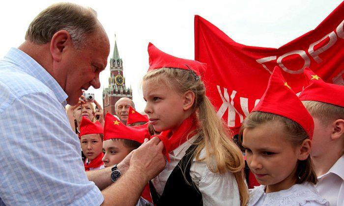 Gennady Zyuganov, líder del Partido Comunista Ruso, ata pañuelos rojos a los cuellos de niños, simbolizando su iniciación en el grupo comunista Jóvenes Pioneros, creado en la Unión Soviética para niños entre los 10 y 14 años. Foto de archivo. Plaza Roja de Moscú. (Alexey SAZONOV/AFP/Getty Images)