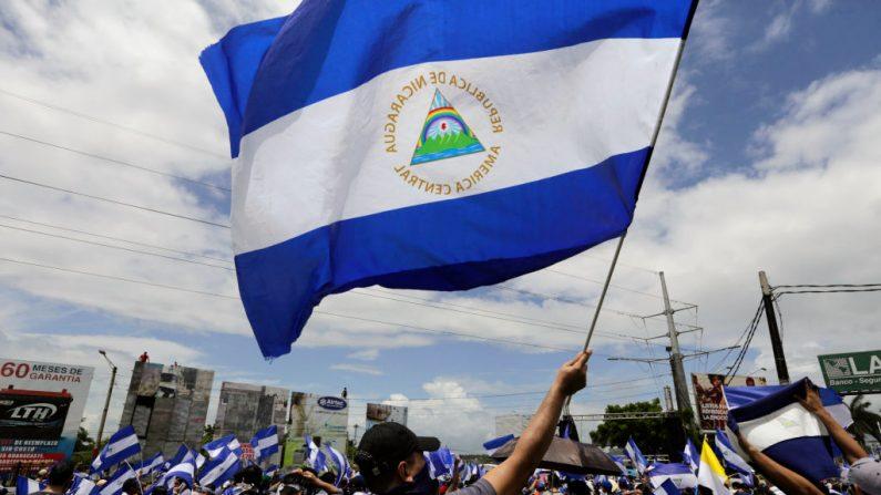 """Un manifestante de la oposición nicaragüense sostiene una bandera nacional, mientras participa en una marcha nacional llamada """"Unidos somos un volcán"""" en Managua el 12 de julio de 2018. (Inti Ocon/AFP/Getty Images)"""