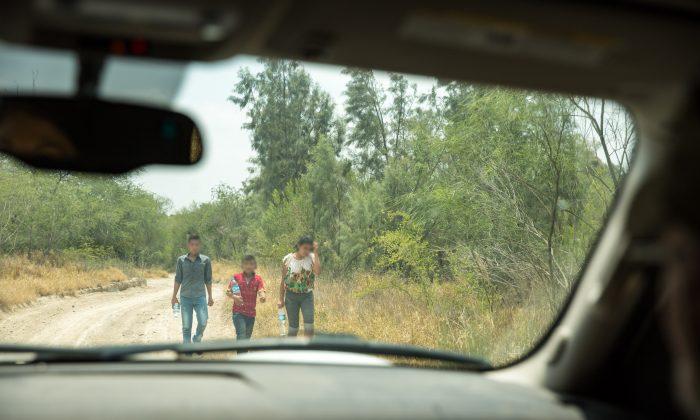 Un grupo de menores no acompañados busca a la Patrulla Fronteriza después de cruzar ilegalmente el Río Grande desde México hacia los Estados Unidos en el Condado de Hidalgo, Texas, el 26 de mayo de 2017. (Benjamin Chasteen/The Epoch Times)