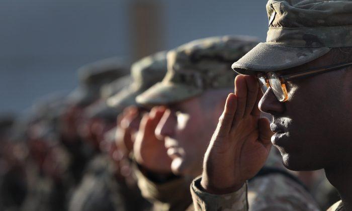 Soldados del Ejército de Estados Unidos saludan durante el himno nacional en una ceremonia de aniversario de los ataques terroristas del 11 de septiembre en el Campo Aéreo de Bagram, Afganistán, el 11 de septiembre de 2011. (John Moore/Getty Images)
