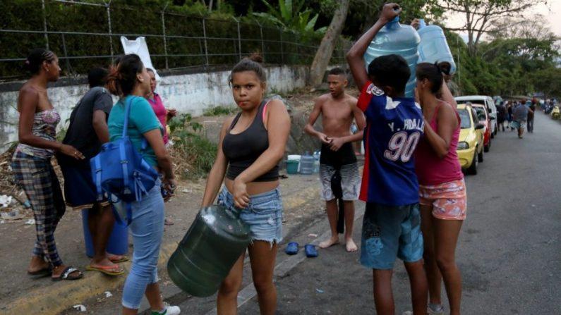 Venezolanos transportan agua que tuvieron que obtener de una fuente natural del cerro El Ávila después de que se suspendiera el suministro de agua en Caracas, Venezuela, luego de un apagón nacional ocurrido el 10 de marzo de 2019. (Edilzon Gamez/Getty Images)