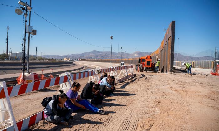 Inmigrantes ilegales salvadoreños esperan a que llegue un transporte después de entregarse voluntariamente a la Patrulla Fronteriza de Estados Unidos por el muro fronterizo que se está construyendo en El Paso, Texas, el 19 de marzo de 2019. (Paul Retje/AFP/Getty Images)