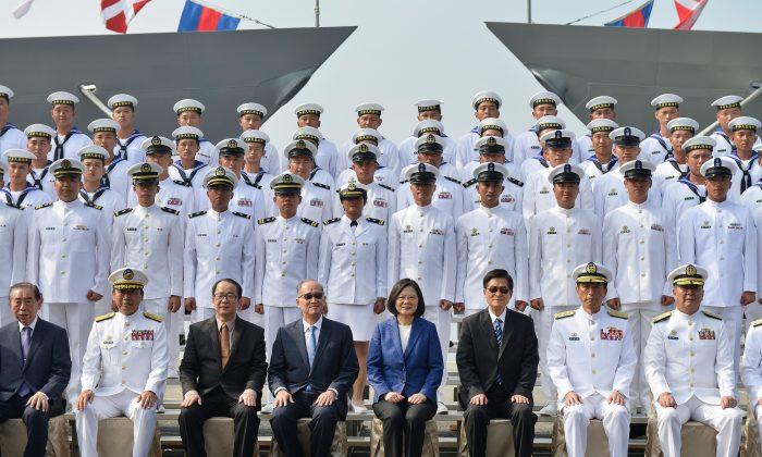 """La presidente de Taiwán, Tsai Ing-Wen (cen. con chaqueta azul), y personal naval reunido participan en una ceremonia para comisionar dos fragatas de misiles guiados de clase Perry de EE.UU. a la Marina de Taiwán, en el puerto sureño de Kaohsiung, el 8 de noviembre de 2018. La presidente Tsai Ing-wen prometió el 8 de noviembre que Taiwán no """"cedería ni un paso"""" en su defensa mientras inauguraba dos fragatas compradas a EE.UU. con el objetivo de aumentar las capacidades navales de la isla contra las amenazas de China. (Chris Stowers/AFP/Getty Images)"""