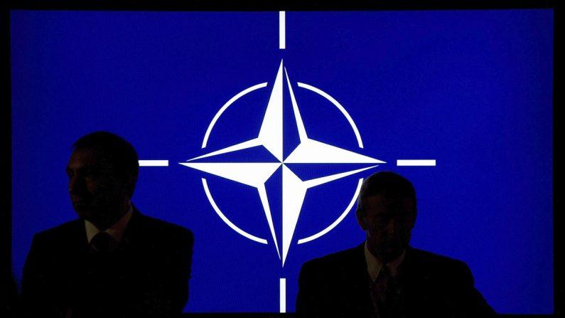 Dos participantes de la cumbre de la OTAN permanecen sentados con el logo de la organización de fondo en el hotel Celtic Manor cerca de Newport (Gales, Reino Unido). EFE/Maurizio Gambarini