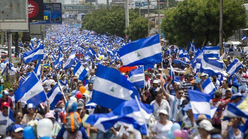 """Miles de personas con banderas de Nicaragua participan durante la """"Marcha de las Flores"""" el 30 de junio de 2018, durante el día número 74 de protestas en contra el régimen de Daniel Ortega, en Managua (Nicaragua). EFE/Jorge Torres"""