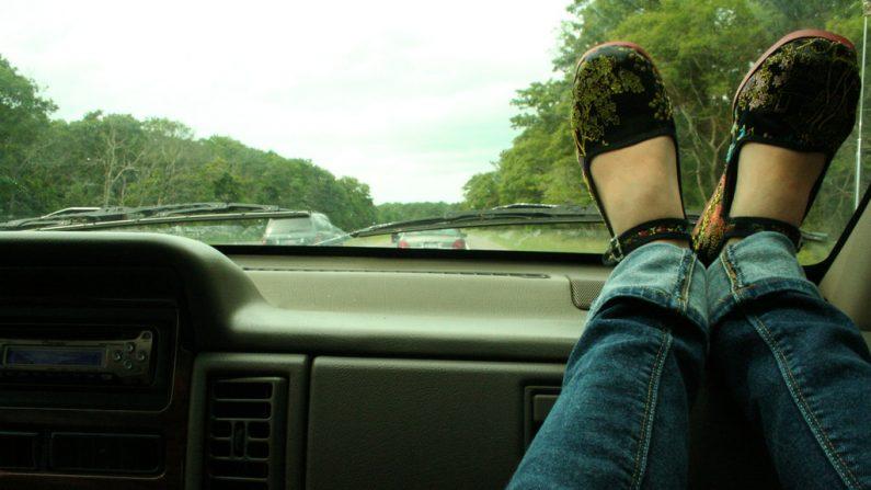 Foto de unos pies apoyados sobre el panel de un automovil. (angela c.   Flickr)
