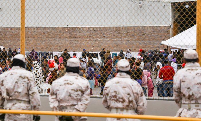 Policía y personal militar mexicano vigilan las afueras de una antigua fábrica donde se encuentran detenidos alrededor de 1800 migrantes centroamericanos en Piedras Negras, México, el 8 de febrero de 2019. (Charlotte Cuthbertson/The Epoch Times)