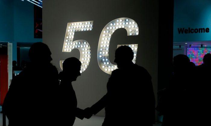 Personas estrechándose la mano frente a un cartel de 5G en el Congreso Mundial de Telefonía Móvil en Barcelona, el 27 de febrero de 2019. (Pau Barrena/AFP/Getty Images)