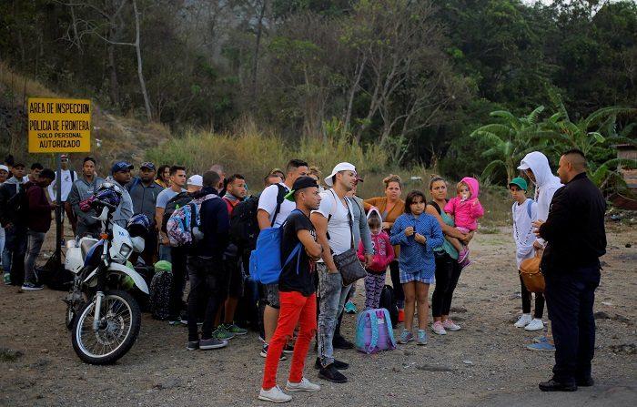 Migrantes cubanos hablan con un agente de migración este viernes al llegar a la Aduana de Agua Caliente (Honduras), fronterizo con Guatemala. En este punto fronterizo se encuentra una caravana migrante convocada por redes sociales y que salió el martes de San Pedro Sula, en el norte hondureño. EFE/ Gustavo Amador
