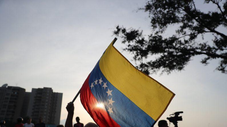 Simpatizantes del presidente encargado Juan Guaidó ondean banderas este martes en la base militar de La Carlota, donde se encuentra Guaidó y un grupo de militares que le apoyan. (EFE/Miguel Gutiérrez)