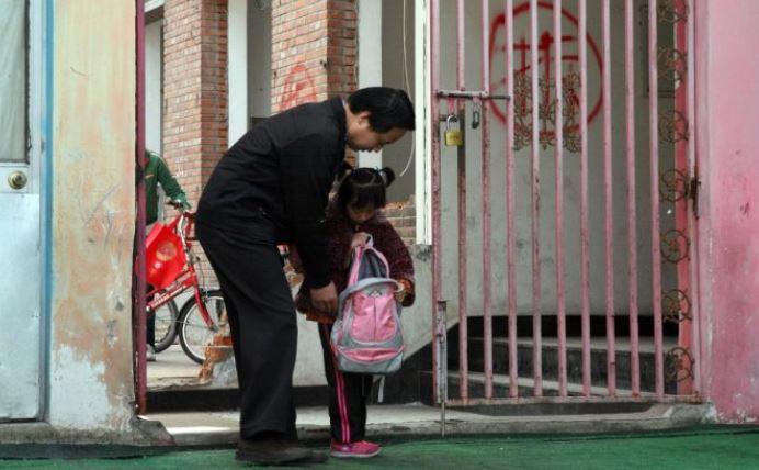 Un padre recogiendo a su hija desde el jardín de infantes. (STR / AFP / GettyImages)
