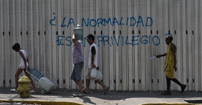 """Durante un nuevo corte de luz en Venezuela, en la Avenida Fuerzas Armadas de Caracas, el 31 de marzo de 2019, la gente pasa por delante de un grafiti que dice """"¿La normalidad es un privilegio? Foto de FEDERICO PARRA/AFP/Getty Images."""