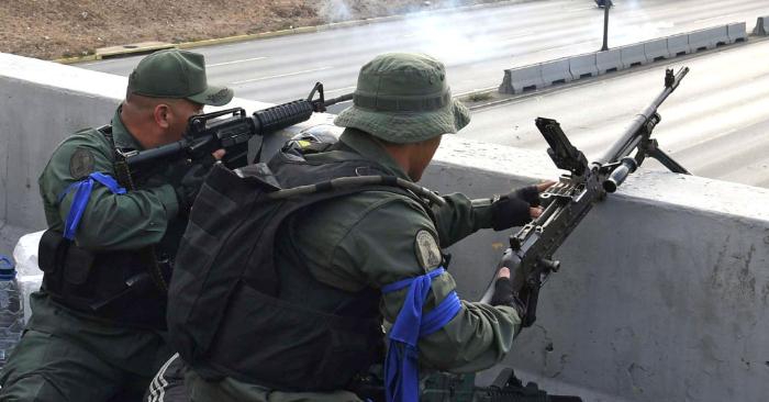 Soldados leales al presidente encargado Juan Guaidó portando cintas azules toman posición frente a la base de La Carlota en Caracas el 30 de abril de 2019. (Foto de Yuri CORTEZ/AFP) (El crédito de la foto debe ser YURI CORTEZ/AFP/Getty Images)