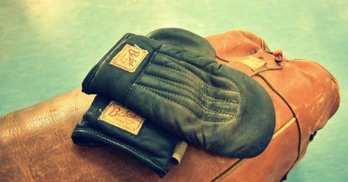 Foto de archivo con fines ilustrativos que muestra unos guantes de boxeo retro colocados en la parte superior de una bolsa pesada. (Pixabay)