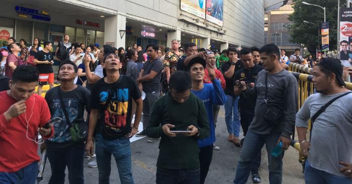 La gente se reúne frente a un centro comercial después de que un poderoso terremoto sacudiera Manila el 22 de abril de 2019. Foto de TED ALJIBE/AFP/Getty Images.