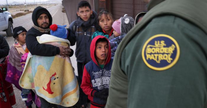 Un agente de la Patrulla Fronteriza de EE.UU. habla con inmigrantes centroamericanos en el muro fronterizo México-Estados Unidos el 1 de febrero de 2019 en El Paso, Texas. Los migrantes fueron puestos bajo custodia buscando asilo político en Estados Unidos. Foto de John Moore/Getty Images.