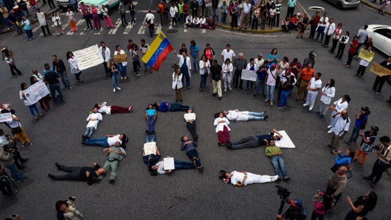 """Trabajadores de la salud se reúnen para formar una cadena humana de lectura """"SOS"""" durante una protesta por la falta de medicamentos, suministros médicos y malas condiciones en los hospitales, frente al Hospital Infantil """"Dr. JM de los Ríos"""" en Caracas el 2 de agosto de 2018. (FEDERICO PARRA/AFP/Getty Images)"""