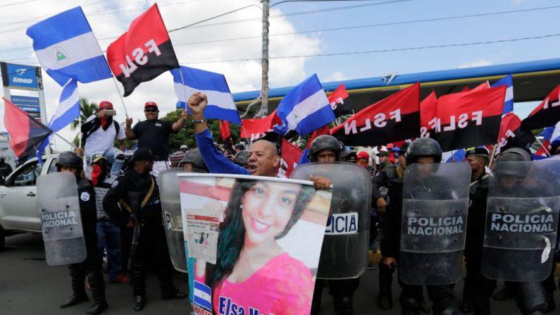 """El nicaragüense Carlos Valle se manifiesta exigiendo la liberación de su hija Elsa Valle del complejo penitenciario """"El Chipote"""", mientras la policía antidisturbios lo separa de los partidarios sandinistas, durante la """"Marcha de los Globos"""" contra el gobierno del presidente Daniel Ortega, en Managua, el 9 de septiembre de 2018. Desde entonces, Carlos Valle ha sido detenido por exigir la liberación de su hija de 19 años, quien fue arrestada al final de una manifestación y permaneció encarcelada en la famosa prisión """"El Chipote"""", donde cientos de jóvenes han sido detenidos desde que comenzaron las protestas contra Ortega en abril. (INTI OCON/AFP/Getty Images)"""