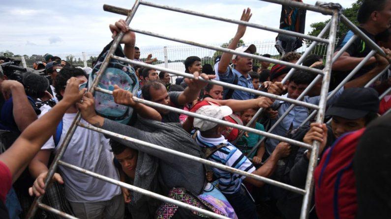 Los migrantes hondureños que se dirigen en una caravana a los EE. UU., eliminan una barrera en el puente fronterizo internacional Guatemala-México en Ciudad Hidalgo, estado de Chiapas, México, el 19 de octubre de 2018, la frontera norte de Guatemala con México. Imagen de archivo. (PEDRO PARDO / AFP / Getty Images)