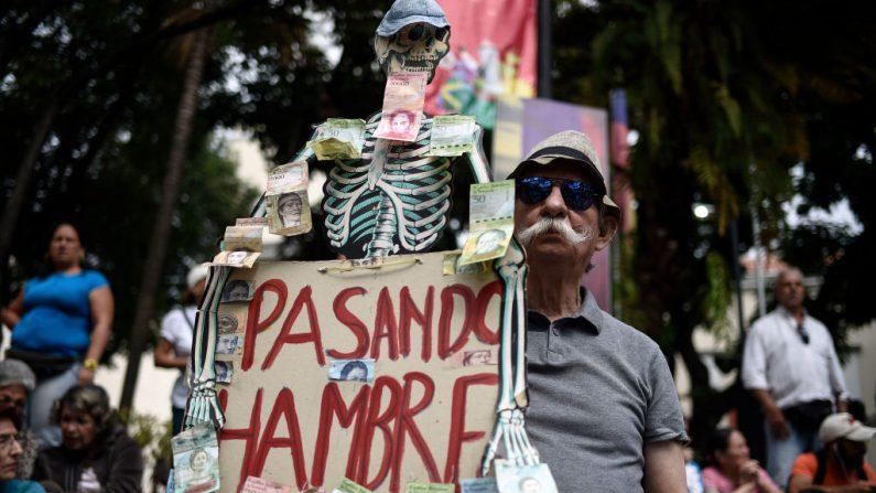 Venezolano sostiene una pancarta con la imagen de un esqueleto humano y el devaluado dinero local mientras espera en la plaza Bolívar en Chacao, al este de Caracas, para escuchar al presidente encargado del país, Juan Guiadó, el 25 de enero de 2019. (FEDERICO PARRA/AFP/Getty Images)