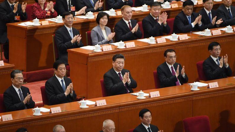 Los líderes chinos (en la fila central desde la izquierda), el miembro del Comité Permanente del Politburó, Zhao Leji, Presidente del Congreso Nacional del Pueblo, Li Zhanshu, el mandatario chino, Xi Jinping , el Primer Ministro, Li Keqiang y el miembro del Comité Permanente del Politburó, Wang Huning, aplauden a Wang Yang (no en la foto), presidente del Comité Nacional de la Conferencia Consultiva Política del Pueblo Chino (CPPCC), que se prepara para entregar su informe durante la sesión de apertura de la CPPCC en el Gran Salón del Pueblo de Beijing, el 3 de marzo de 2019. (GREG BAKER/AFP/Getty Images)