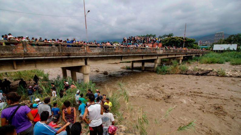 """Venezolanos cruzan el bloqueado puente internacional Simón Bolívar, en Cúcuta, Colombia, en la frontera con Venezuela, mientras otros miran desde la orilla del río Táchira, el 2 de abril de 2019. Después que el nivel del río Táchira subió, las """"trochas"""" fueron inundadas y los venezolanos que necesitaban cruzar a Colombia y regresar, escalaron contenedores y caminaron a través del bloqueado puente Simón Bolívar en un intento desesperado por atravesarlo. (SCHNEYDER MENDOZA/AFP/Getty Images)"""