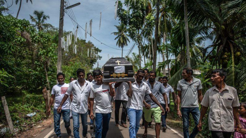 Un ataúd es llevado a un lugar de entierro durante un funeral masivo en la Iglesia de San Sebastián el 23 de abril de 2019 en Negombo, Sri Lanka. Al menos 311 personas murieron y cientos más resultaron heridas después de que ataques coordinados contra iglesias y hoteles el domingo de Pascua sacudieran tres iglesias y tres hoteles de lujo en Colombo y sus alrededores, así como en Batticaloa, en Sri Lanka. (Carl Court/Getty Images)