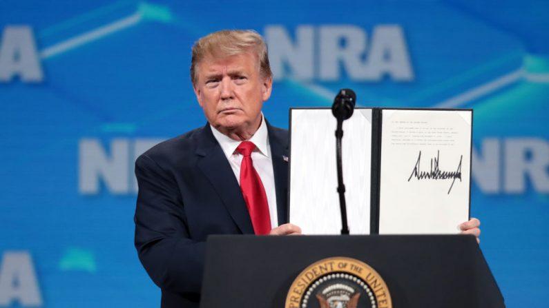El presidente de Estados Unidos, Donald Trump, muestra a la multitud un documento firmado rechazando el Tratado sobre el Comercio de Armas de la ONU en el Foro de Liderazgo de la NRA-ILA en la 148ª Reunión Anual de la NRA el 26 de abril de 2019 en Indianápolis, Indiana. (Scott Olson/Getty Images)