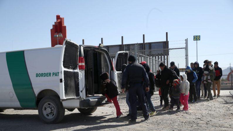 Un agente de la Patrulla Fronteriza de Estados Unidos carga a los migrantes detenidos en una camioneta en la frontera entre ese país y México el 31 de marzo de 2019 en El Paso, Texas. Foto de Justin Sullivan/Getty Images.
