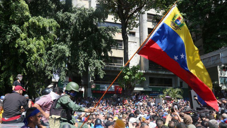 Un oficial militar desertor, que se unió a los partidarios de Juan Guaidó, ondea una bandera venezolana en la Plaza Altamira el 30 de abril de 2019 en Caracas, Venezuela. (Edilzon Gamez/Getty Images)